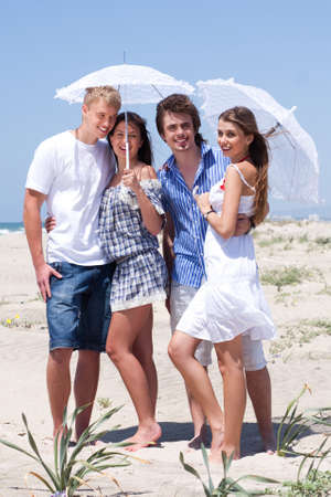 Adorable young couples under an umbrella on sand beach and posing in style photo