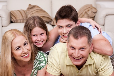 Smiling family lying together on the floor in living room photo
