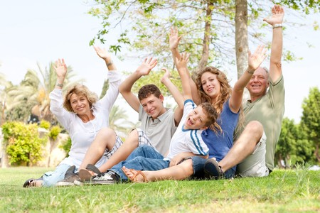 family sitting in a park and waving hands photo