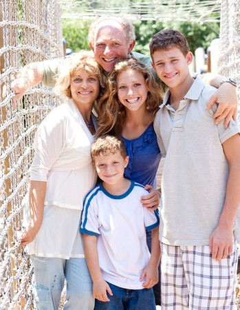 closeup of happy family standing on a hanging bridge photo