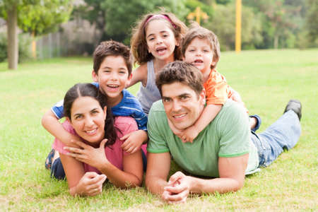 Happy family of five lying in the park and smiling at camera photo