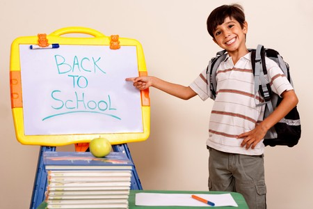 Smiling school boy pointing at white board on his classroom photo