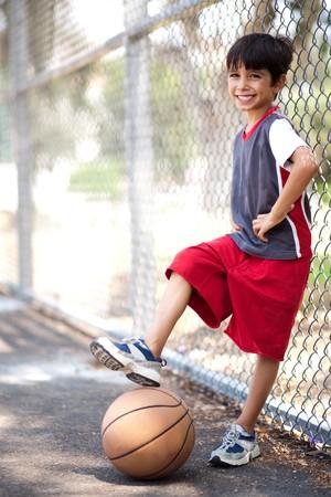 Cute chico junior de baloncesto en virtud de su pierna, posando en estilo