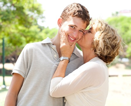 Portrait of a happy old woman kissing her adorable grandson photo