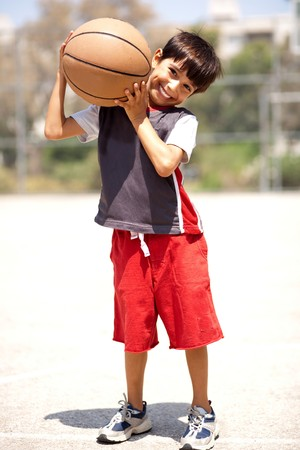 Boy with basketball on his shoulders, outdoors Stock Photo