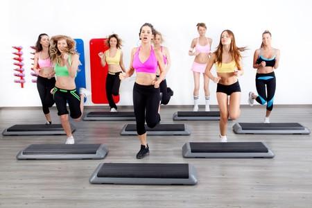 gimnasia aerobica: imagen de grupo de mujeres en una clase de pasos en el gimnasio  Foto de archivo