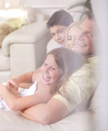 Happy family smiling and looking  behind the window glass in living room photo