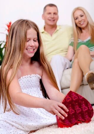 Happy young girl opening a gift box with her parents in living room photo