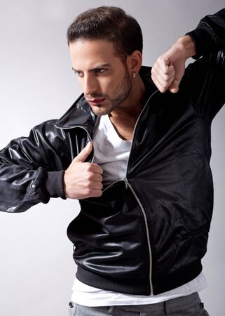 Smart male model giving movement with black jacket on a isolated grey background Stock Photo - 7847262
