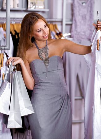 Fashion model picking her choice as she holds shopping bags in her hands photo