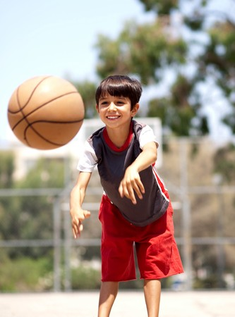 Young boy in action passing basketball