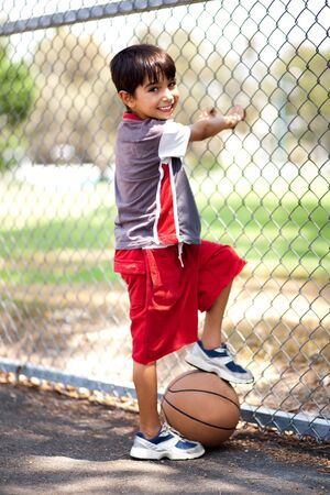playground basketball: Smart kid posing with basketball as he holds it under his leg