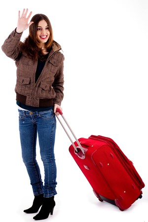 farewell: young woman waving hand holdin luggage