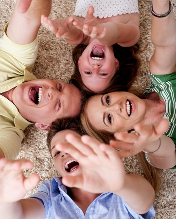 Happy family of four lying on the carpet and having gala time Stock Photo - 7882580