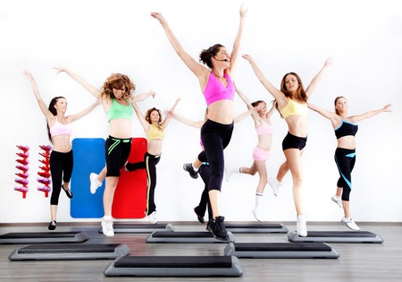 group of women doing aerobics on stepper in gym