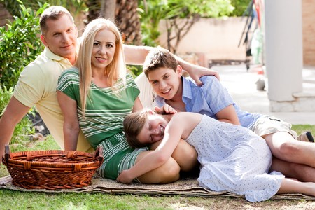 Lovable family of four relaxing during sunny day and looking at camera photo