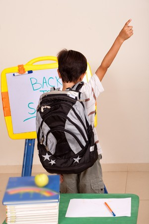 Rear view of a young student with back pack and raised arm photo