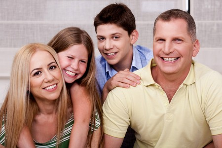Affectionate family of four smiling at camera and having fun Stock Photo - 7957849