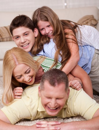 Full portrait of a happy family lying on bed and having great time photo