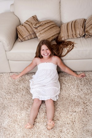 Beautiful little girl sitting on carpet and resting against couch photo