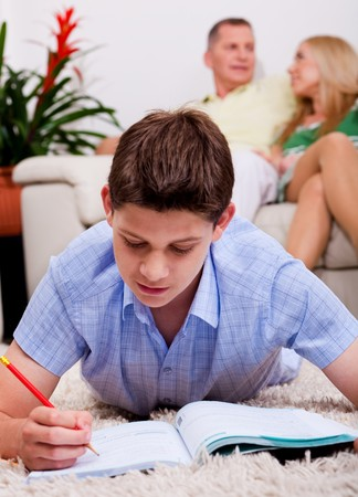 Young buy busy with his books and study material lying on carpet with family in the background photo