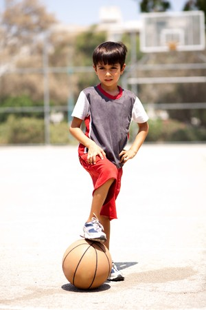 Smart kid holding basketball under his leg and posing in style in front of camera photo