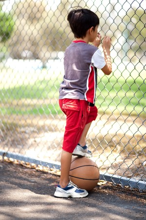 Rear view of young basketball player holding ball under his leg and and looking through fence photo