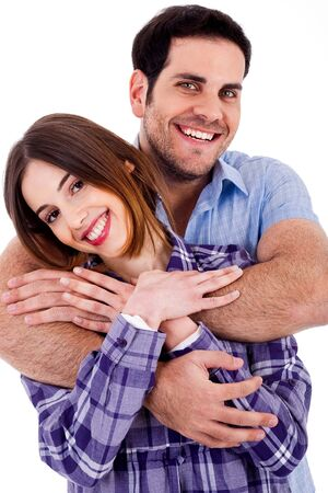 Closeup portrait of a cute young man hugging his wife from behind photo