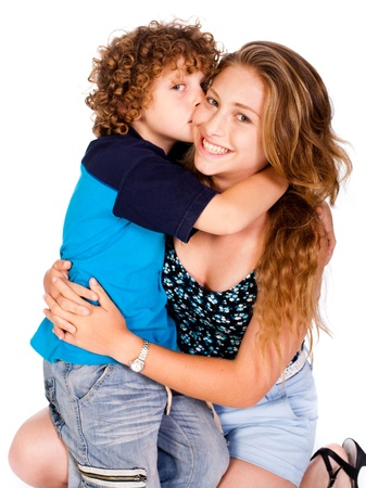 Young kid kissing his mom and looking at camera, isolated on white.. Stock Photo - 9796462