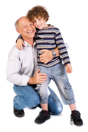 grandsons: Grandfather embracing his grandson, indoors against white background..
