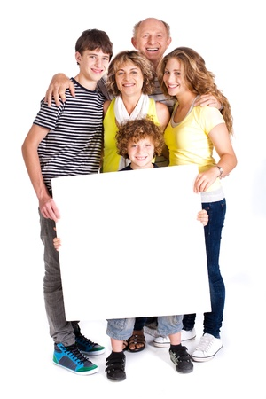 Portrait of a happy family holding a billboard isolated over white background..