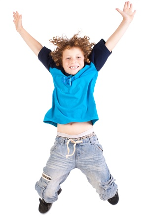 Young and attractive kid jumping high, indoors, isolated against white background...