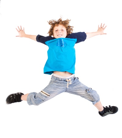 Attractive young kid jumping high, indoors. photo