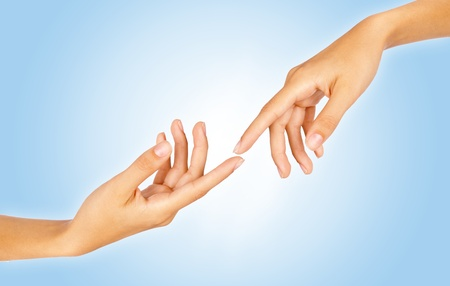 Close-up of two finger tips reaching out each other over gradient blue background photo