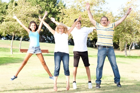 widespread: Family - Mother, Father, Children jumping with wide-spread raised arms in park.