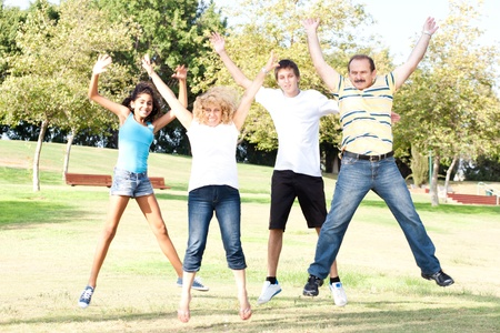 Family jumping high in the air on a green meadow at a late summer afternoon... photo