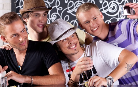 group of young adults: Self portrait of handsome bunch of guys drinking and enjoying in nighclub.