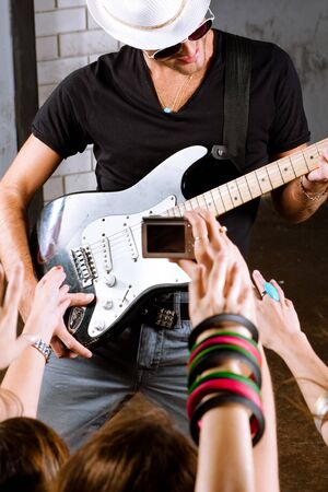 Rock guitarist playing in front of a cheering crowd. photo