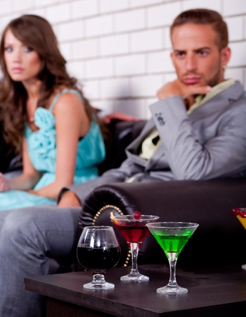 Annoyed young couple in the backround in bar or night club with colorful drinks in focus. photo
