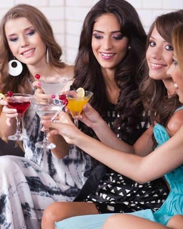 Group of happy girls smiling and partying in a bar or a nightclub.. photo