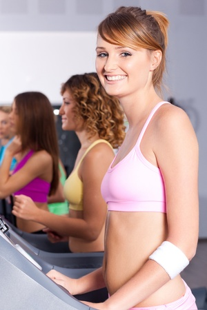gym class: Young fit woman doing cardio exercise and posing in front of camera..