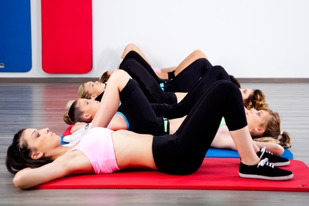 Group of young women in the gym centre performing aerobics.