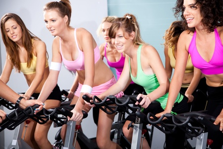 Four people on bicycles in a gym or fitness club for a workout. Stock Photo