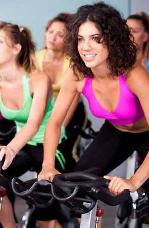 cardio fitness: Group of four people spinning in gym or fitness club exercising their legs doing cardio training.