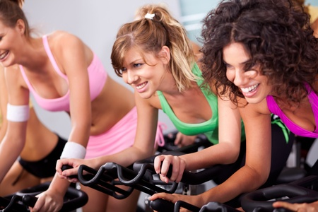 Gorgeous young females cycling in spinning class in gym.
