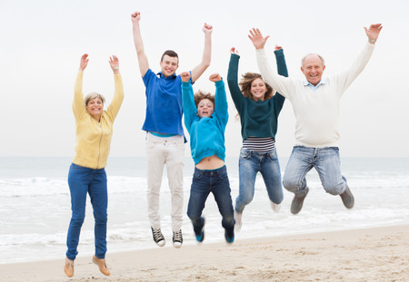 Happy family jumping on the air at beach Stockfoto