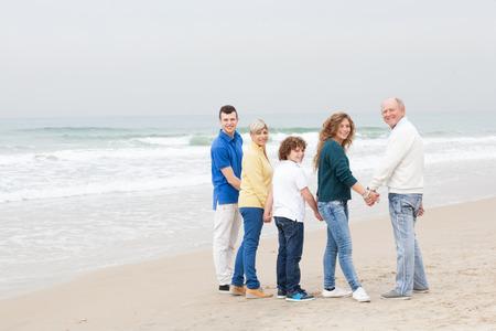 La famille élargie en regardant en arrière à la caméra Banque d'images