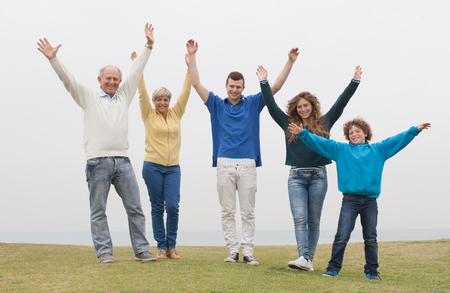 hands raised: Happy family standing on lawn, hands raised