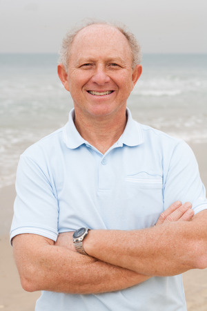 Smiling senior man standing at beach, arms crossed photo