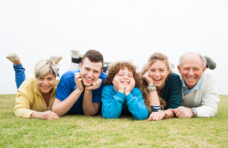 Excited happy family lying down on the grass
